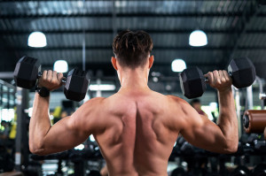Back view of attractive portrait man lifting dumbbells with both